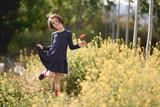 Little girl walking in nature field wearing beautiful dress - 192794306