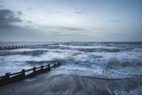 Beautiful dramatic stormy landscape image of waves crashing onto beach at sunrise - 192795777