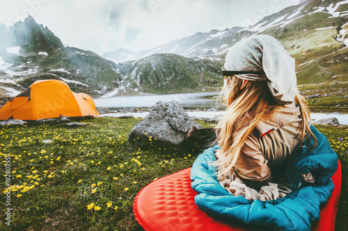 Camping travel vacations woman relaxing in sleeping bag on mat enjoying mountains landscape Lifestyle concept adventure weekend outdoor harmony with nature