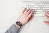Businessman hand working on computer keyboard wearing a watch