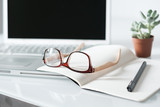 Office desk with eyeglasses and computer laptop