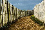 Coastal sandy trail, wooden fences on both side and dark cloudy sky, in Brittany, France - 192816310