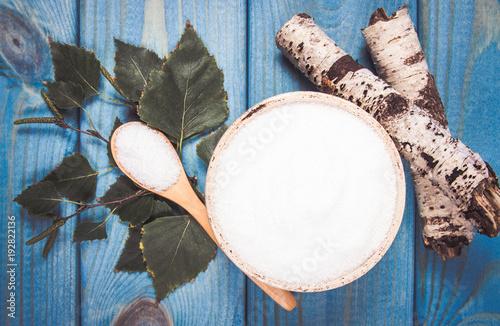 Xylitol - sugar substitute. Birch sugar on blue wooden background. - 192822136
