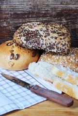 fresh wheat and rye buns with sesame seeds, linseed and pumpkin seeds and sunflower seeds cut with knife