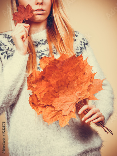 Woman holding bouquet made of autumn leaves