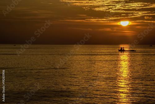 Foto op Aluminium Zee zonsondergang Golden hours in ocean with boat under sun light.