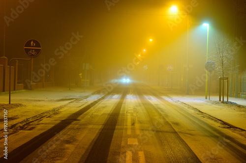 Tuinposter Nacht snelweg Ulica w zimową noc pokryta sniegiem i ślady samochodów.