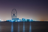 The Ain Dubai ferris wheel under construction, night cityscape with illumination, Bluewater Island, Dubai, UAE.