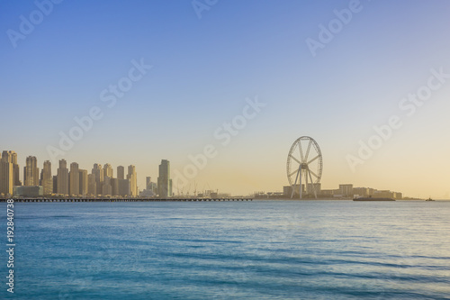 The Ain Dubai ferris wheel under construction, sunset over Bluewater Island, panoramic view of cityscape, Dubai, UAE.