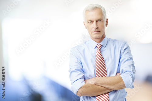 Wall mural Confident professional businessman portrait. An executive male sales manager standing at the office and looking at camera.