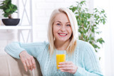 Woman drinking orange juice smiling. Beautiful middle aged Caucasian model face closeup.