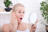 Middle aged woman looking at wrinkles in mirror. Plastic surgery and collagen injections. Makeup. Macro face. Selective focus - 192853107
