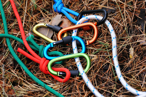 Carabiner with rope on nature background.