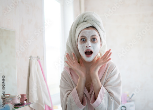woman looks after the face makes a mask