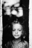 Black white psychological detailed portrait of young little child through abstract reflected window. Early life of innocent baby. Expressive strong emotional kid look. Different facial expressions.