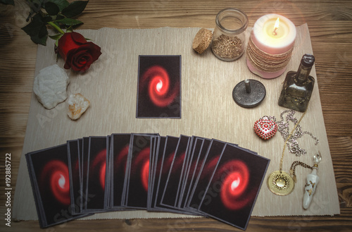 Tarot cards and rose flower on fortune teller desk table background