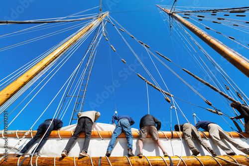Canvas Zeilen Crew leans over the side of a big sailboat to raise the heavy sail on a tall ship at sea. Takes six strong people to hoist the canvas sail. Theme for teamwork, cooperation