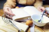 Open recipe book in the hands of an elderly woman - 192893582