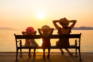 Family with children at sunset by the sea