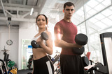 Waist up portrait of fit sportive couple posing with dumbbells looking at camera in modern gym