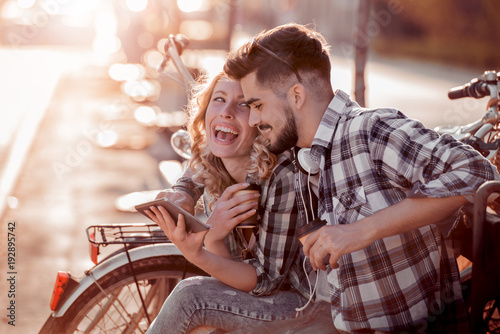 Couple in love enjoy together on a bench with bikes.