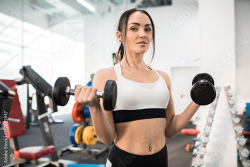 Portrait of sportive young woman training with dumbbells in modern gym and looking at camera, copy space