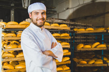 Baker. Bakery. A young handsome worker at a bakery on the background of a rack with ready-made bread. Industrial production of bakery products. a man in a special baker's clothes. Portrait. Working