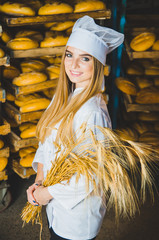Bakery. Bread. Girl Baker. Young beautiful girl. Worker of a bakery on a background of racks with bread and spikelets of wheat in hands. Industrial production of bakery products. Cap