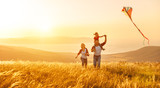 Happy family father of mother and child daughter launch a kite on nature at sunset - 192900547