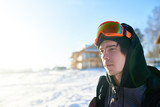 Portrait of handsome young snowboarder looking away enjoying sunny summer day at ski resort with wooden chalets in background, copy space - 192901104