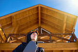 Low angle portrait of handsome young snowboarder against wooden chalet at modern ski resort enjoying sunny winter, copy space - 192901172
