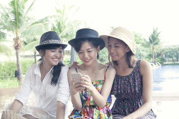group of young asian woman friend watching on smart phone screen with toothy smiling face happiness emotion
