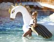 Quadro woman standing on sea shore beach near resort hotel with giant inflatable unicorn pegasus float mattress in white bikini
