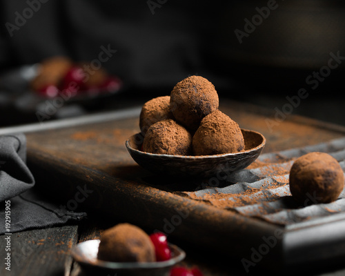 Chocolate truffle. Dark chocolate and cherry candy sprinkled with cocoa on a dark wooden background in rustic style. Atmospheric food photo. Homemade fresh energy balls.
