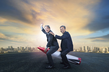 two senior business man riding on children rocket toy standing on asphalt ground with urban scene background for humor business concept