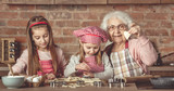 Little girls making cookies with her granny - 192926953