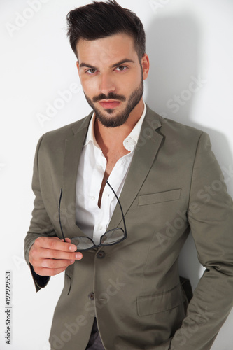 handsome smart casual man holding glasses