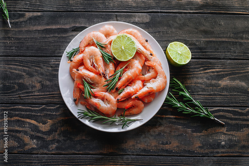 Raw shrimp with lime and rosemary on a wooden table top view - 192930172