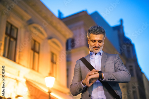 Wall mural Mature businessman with a smartwatch in a city.