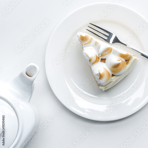 top view of delicious piece of cake with meringue and teapot on white table