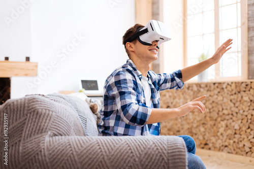 Amusement. Delighted well-built stylish adolescent smiling wearing a VR headset and sitting on the sofa and touching the imaginary picture