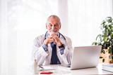 Senior doctor with laptop sitting at the office desk. - 192938121