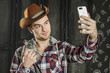 Portrait of a Cowboy. dark hair, jeans , plaid shirt. he holds the chinchilla animal . photographing self on smartphone
