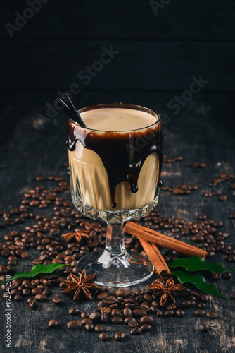 A fragrant cup of cocoa with milk and chocolate on a black wooden background. Top view. Copy space.