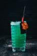 Quadro Alcohol Cocktail Blue Lagoon. Orange, liquor, ice. On a black wooden background.
