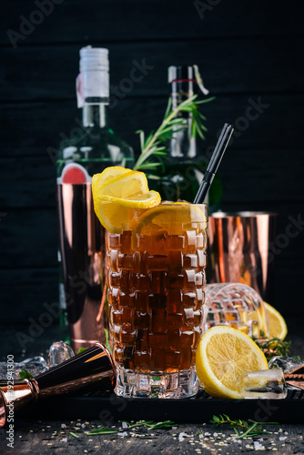 Alcohol cocktail Long Island. On a black wooden background.