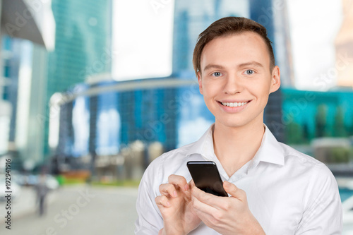 Young man typing text message on his cellphone