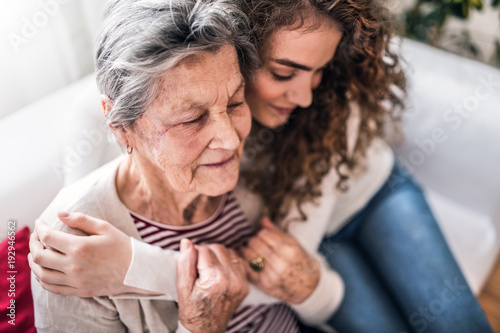 A teenage girl with grandmother at home, hugging. - 192946562