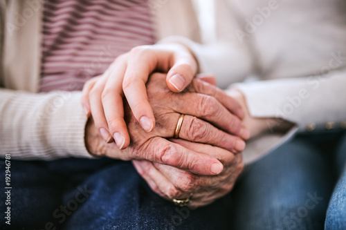 Hands of teenage girl and her grandmother at home.