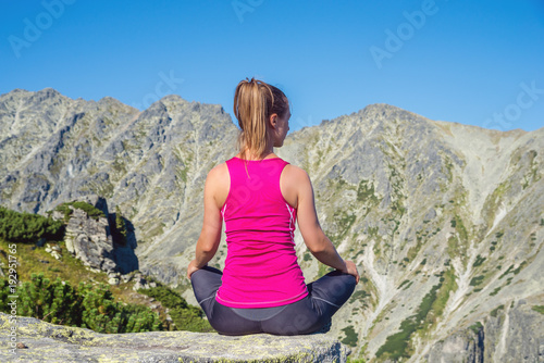 Foto op Canvas Zen young woman meditate on top of the mountain